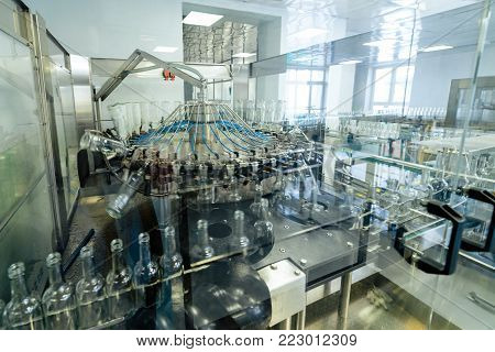 Mechanism of grabbing and turning over of bottles, automatic machine for washing glass bottles. Production and bottling of alcoholic beverages.