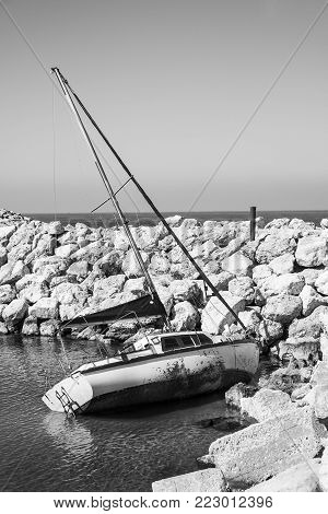 Breakwater protecting the beach of Mediterranean sea in Israel. Yacht floating on the side after the crash in the port of Tel Aviv. Black and white picture