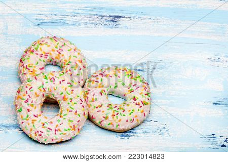 Traditional donuts on blue wooden background. Tasty doughnuts with icing, copy space