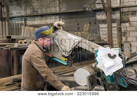 LIPETSK, RUSSIA - JUNE 15, 2017: Lipetsk Machine Tool Plant. The worker makes the sawing of the metal workpiece on a band saw.