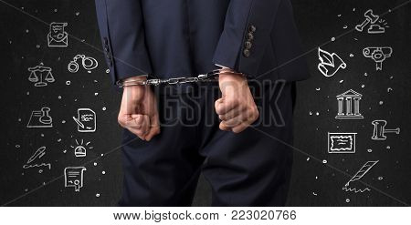 Chalk drawn courthouse symbols and close handcuffed hands in suit
