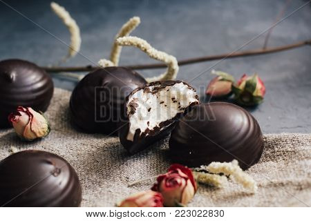 marshmallows in chocolate glaze, part of one bitten off on rustic background. Decorated with dry flowers of roses