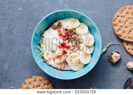 Oatmeal with jam and bananas in a turquoise plate. Morning breakfast with bread. Healthy eating. dietary and vegetarian food. Swedish bread on blue background. millet porridge top view