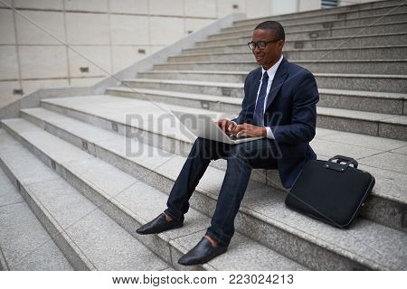 Smiling young businessman sitting on steps and working on laptop