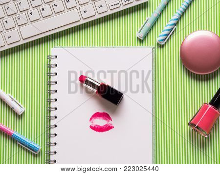 Girlish flatlay with keyboard, notebook with kiss and makeup accessories. Girl's blog valentine's day concept