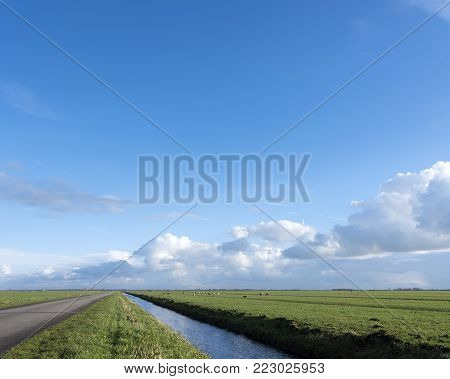 country road and canal between vast expanse of meadows in dutch eempolder in holland under cloudscape