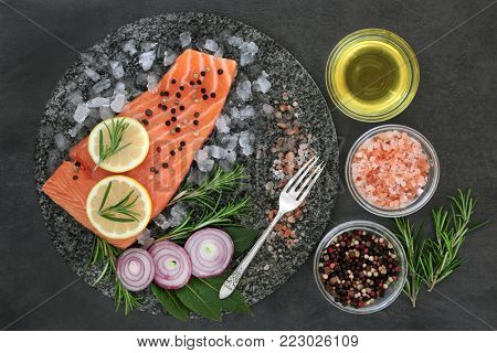 Salmon on crushed ice with herbs, himalayan salt, lemon fruit, onion, peppercorns and olive oil on marble slab on slate background. Healthy heart food high in omega 3 fatty acids.