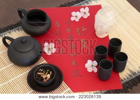 Jasmine tea used in Chinese herbal medicine with cherry blossom, Buddha head  and tea set with calligraphy script. Translation reads as acupuncture is a traditional and effective medical solution.