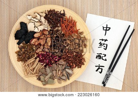 Chinese traditional herbs used in alternative herbal medicine on a wooden plate and bamboo background with calligraphy script. Translation reads as chinese alternative medicine. Top view.