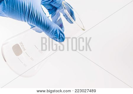 hand of scientist hold empty chemical laboratory beaker. Research science and medical laboratory.