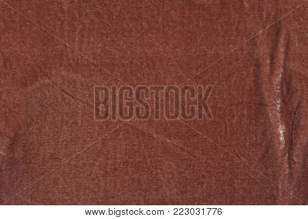 The texture of brown velvet fabric with folds