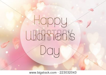 Abstract composition for Women's Day. Pink flower petals flying with hearts symbols, defocused background.