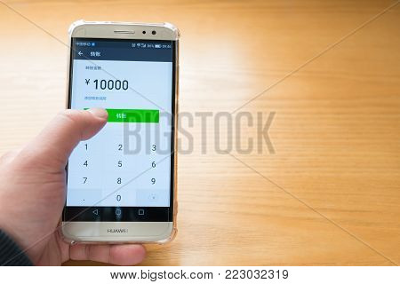 Zhongshan,China-January 13, 2018:Chinese man using mobile to transfer money.Mobile for payment and money transferring becomes very common and popular in China.
