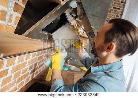 Cooker hood. Pleasant brunette male cleaner removing cooker hood for cleaning it and holding cleaning cloth