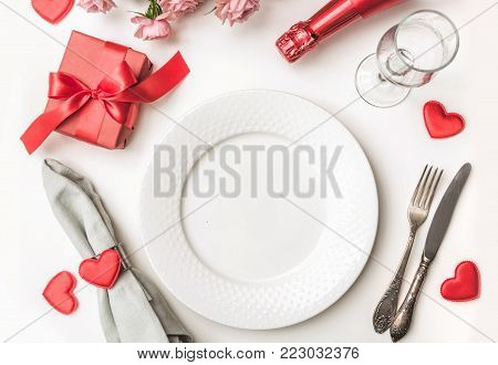 Valentines Day Dinner With Table Place Setting With Red Gift, A Bottle Of Champagne, Hearts With Sil