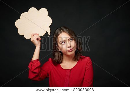 Thinking contemplating woman holding an empty thought bubble and looking away at blank copy space, over dark background