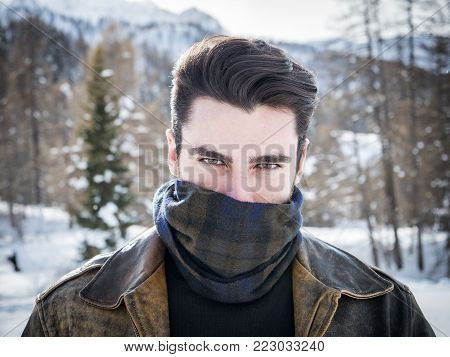 Portrait of adult handsome man covering face with scarf looking provocatively at camera.