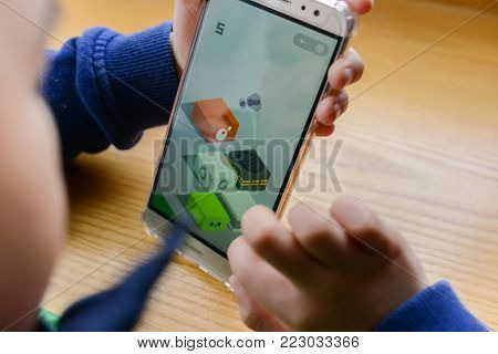 Zhongshan,China-January 7,2018:kid playing mobile game inside Wechat own by Tencent.Tencent creates lots of popular mobile games & this Jumping game spreads out very fast in the new year of 2018.