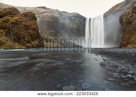 Spectacular landscape in Iceland with a waterfall which falls down from the cliff. River has rocky shores and cliffs covered by faded grass and moss. Horizontal.