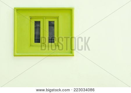 Painted green closed window on white wall with copy space