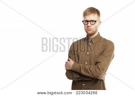 Human facial expressions, emotions, feelings, reaction, attitude and life perception. Studio shot of reluctant stubborn young Caucasian bearded man crossing arms and looking seriously at camera