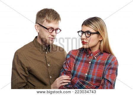 Picture of mysterious young unshaven male in eyeglasses and brown shirt holding arm of frightened blonde female who is looking at him with suspicious and disgusted expression, frowning her eyebrows