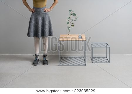 Woman stands in the studio on the gray wall background. Next to her there are two wooden-metallic stands with green branch in the glass vase and small support. Horizontal.