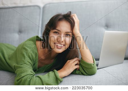 People, leisure, relaxation and modern technologies concept. Happy young Latin woman with pretty smile having joyful relaxed look whole lying on large blue sofa with open laptop computer pc