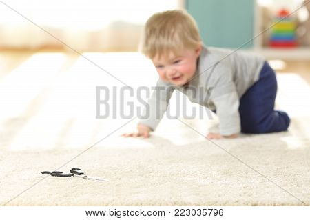 Baby in danger crawling towards a scissors on a carpet at home