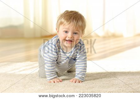 Happy baby crawling towards camera and looking at you on a carpet at home