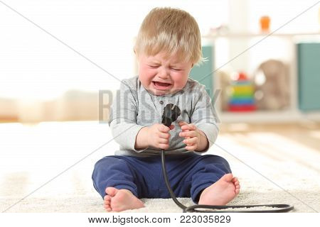 Front view portrait of a baby aby in danger crying holding an an electric plug sitting on the floor at home