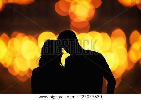 Silhouette of a couple with de-focused / bokeh lights.