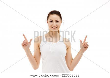 Woman pointing fingers up above her isolated on white background