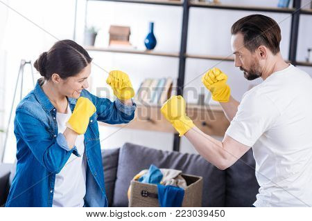 Adorable fight. Pleasant appealing nice couple posing in profile while dressing in gloves and opposing
