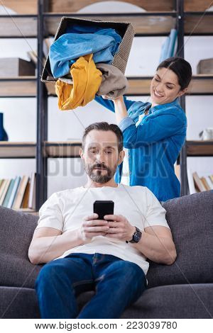 Funny punishment. Attractive bearded confident husband sitting on the coach and playing on the phone while wife dropping clothes at him