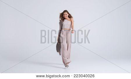Full-length shot of beautiful girl in top and trousers walking towards camera