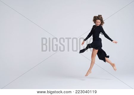 Full-length shot of cheerful beautiful young woman hovering in the air