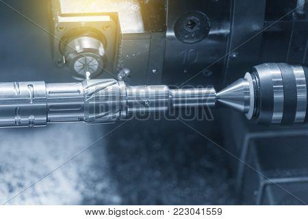 Close up of the CNC lathe (Turning machine)cutting brass shaft. Hi-precision CNC machining concept.