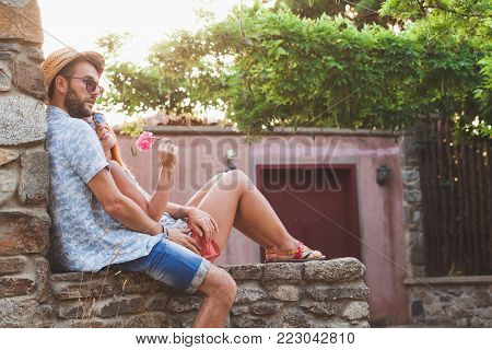 Young couple in love sitting on the wall