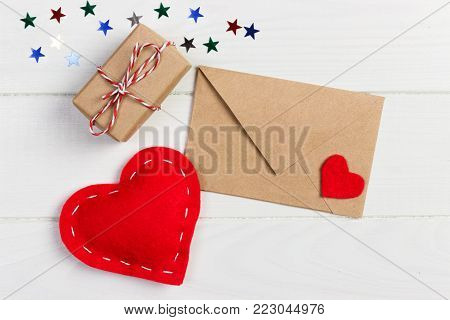 Valentine with red heart. A paper parcel wrapped tied. A red heart with gift box wrapped with paper kraft.