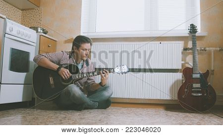 Young man composes music on the guitar and play in the kitchen, other musical instrument in the foreground, sitting