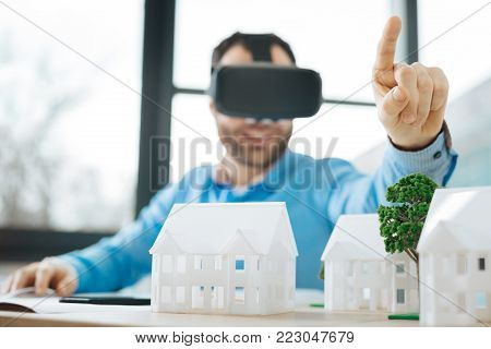 New experience. Charming upbeat young engineer sitting at the desk full of house models and testing a VR headset while pointing at something with his finger