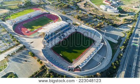 Nicosia, Cyprus - 25/12/2017: Aerial bird's eye view of GSP football stadium and highway A1 at Latsia.Soccer field, athlete track, seats, auxiliary pitch of Pancyprian Gymnastic Association from above