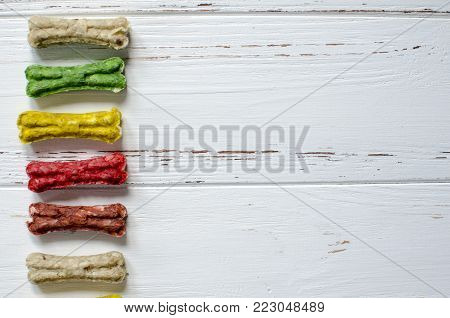 Delicious chewing colored bones for dogs with different tastes on white wooden background