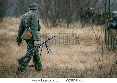 German soldier with machine gun goes to position