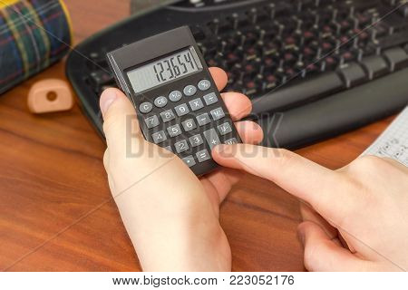 Modern electronic pocket calculator with a liquid-crystal display in the hand of schoolboy on a blurred background of the desktop part