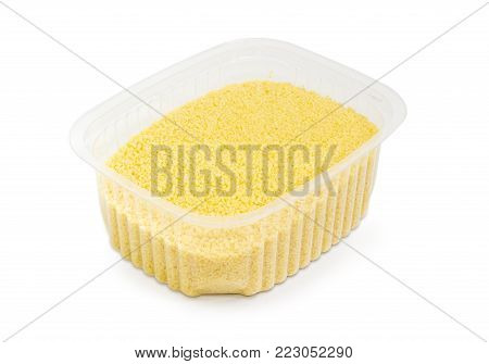 Uncooked couscous in the small semi transparent plastic container on a white background