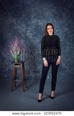Beautiful young  brunette woman, wearing black blouse and dark blue pants, standing in a room with gray walls and houseplant with colorful leaves on a wooden chair
