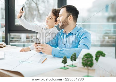 Precious moment. Upbeat little boy sitting at the table in the office of his father and taking a selfie together with him