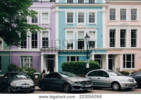 LONDON, UK - MAY 17, 2016: People walk past colourful terraced houses of Primrose Hill. Primrose Hill is one of the most expensive residential areas in London, UK